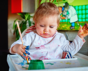 Cute little girl painting with brush.
