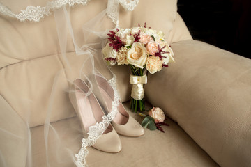Bridal shoes and wedding bouquet on armchair