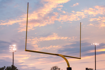 American football goal posts against sunset