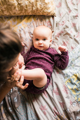 Woman kissing baby on bare feet
