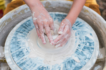Childs hands spinning clay on pottery wheel