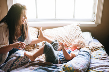 Mother and young son playing on bed
