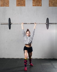 Woman athlete doing a front lunge with a barbell over his head in the crossfit gym