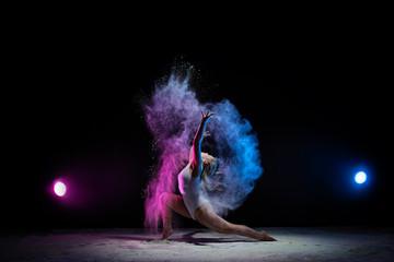 Young girl posing in color dust cloud in studio