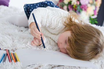 Smiling beautiful little girl drawing colored pencils lying on a bed