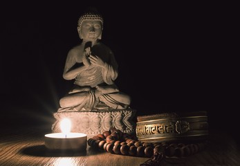 Stone Buddha statue on wooden floor with candle