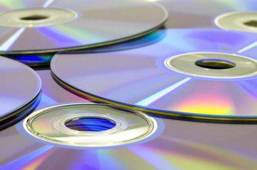 Many CD or DVD disc media laying on table