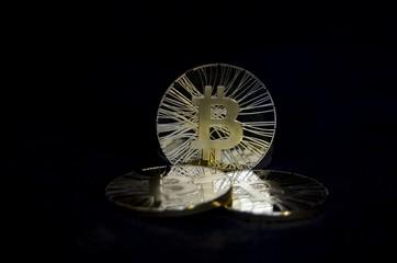 Three shiny bitcoin coins on black background