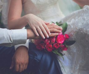 Wedding couple, bride and groom, hands with rings and pink gentl