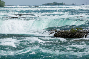 Foto op Plexiglas Kust The bright blue water of Niagara Falls flows down the river and over the waterfall in spring