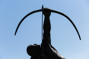 Bronze statue of a native american archer points his bow into the sky