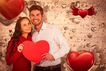 Composite image of happy couple holding paper heart 3d