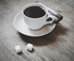 cup of coffee with two chocolate rolls and two sugar cubes on the wooden table