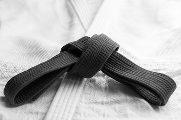 Black judo, aikido or karate belt tied in a knot with white kimono in background