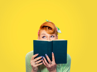 beautiful pinup retro hair style girl hiding herself behind a book isolated yellow background copy space