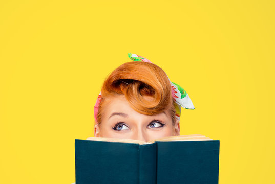 picture of cropped image close up head shot of pin up retro hair style woman holding green book looking up to copy space thinking isolated yellow background