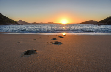 Beautiful sunrise with the sun rising from the Atlantic Ocean, solar path on the water and footprints at the deserted Praia Vermelha Beach, Rio de Janeiro, Brazil