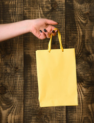 yellow shopping bag in female hand on wooden background