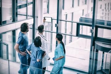 Surgeons and nurse looking at digital tablet