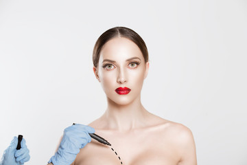 Bust plastic correction isolated white grey background. Closeup portrait half naked beauty woman looking at you red lips outlines on breast by plastic surgeon hands before plastic surgery implants