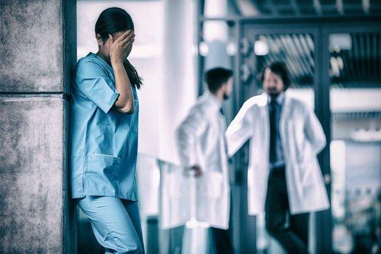 Stressed nurse standing in hospital