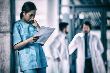 Thoughtful nurse examining medical report