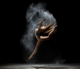 Graceful girl dancing in white dust powder