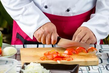 chef  peeling garlic on wooden boards