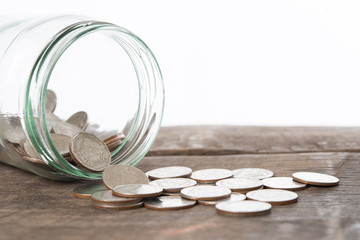 Saving money concept of collecting coins on wooden background.