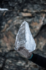 Triangle shaped ice block in hands in front of stone background