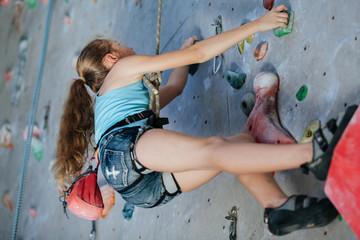 One teenager climbing a rock wall indoor.