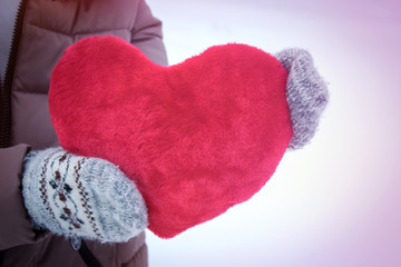The woman in mittens holding a big red heart on a snow background. for Valentine's day