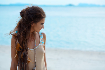 Beautiful young woman walking by the shore line on the beach