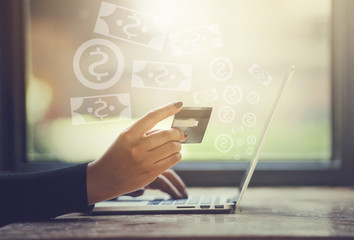 Woman Hands holding credit card and using laptop. Online shopping and get money from internet