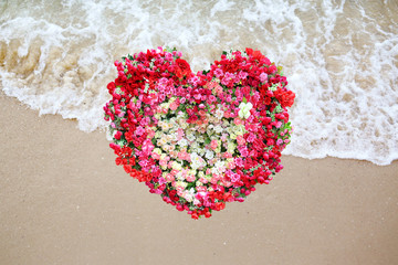 Heart Made of Roses flower on beach background.