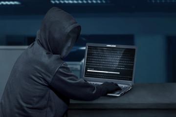 Hacker man wearing mask using laptop to upload computer virus