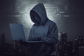Hooded hacker holding laptop while typing