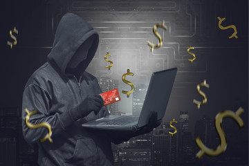 Hooded man wearing anonymous mask and holding laptop while showing credit card