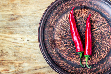Some chili peppers on dark plate, fresh red ripe hot chilli on old wood board background with copy space, guinea pepper or bird pepper, small capsicum, fiery chilli.