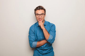 man wearing glasses, smiling and touching his chin