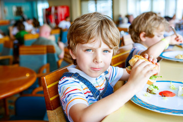 Cute healthy preschool boy eats hamburger sitting in school canteen