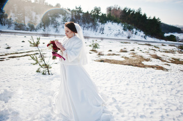 Portrait of cute brunette bride with bouquet on hands at frost a