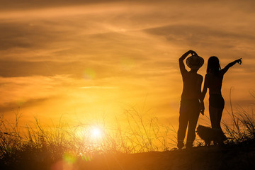 silhouette of couple in love on the beach at sunset. pointing to