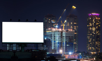 Blank billboard, construction crane and building in the night