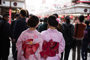 Couple Japanese women in traditional attires visiting a sacred buddhist temple in Tokyo. On the background, parts of the shrine and crowds of people are seen.