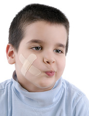 Child with band aid on his cheek looking at the space for your text.