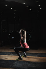 Strong sporty girl doing squats with barbell