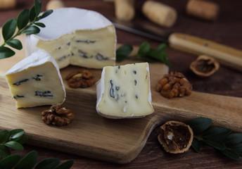 сыр камамбер с голубой плесенью на деревянной разделочной доске