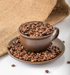 Coffee cup with roasted coffee beans.