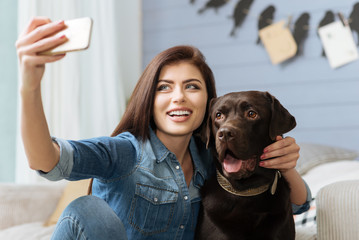Elegant cheerful lady and her pet posing for a shot